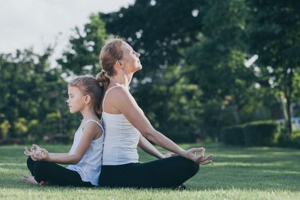 Mutter und Tochter im Park in Meditationshaltung, praktizieren Yoga